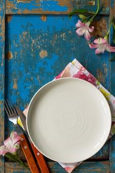 Réglage de la table du printemps ou de la fête des mères couverts et serviette de table sur une table en bois