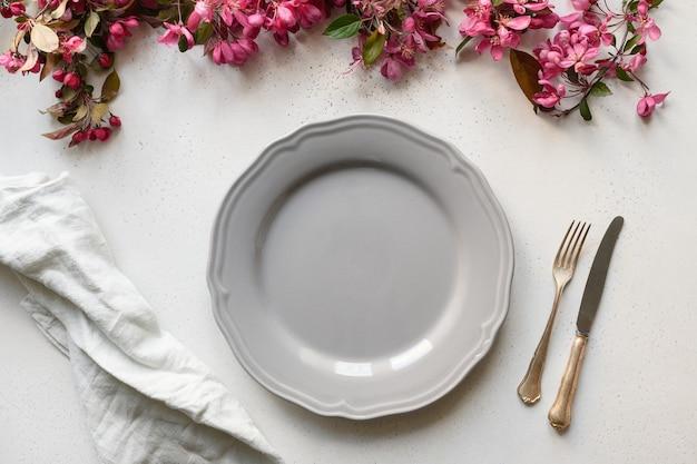 Réglage de la table d'élégance avec des fleurs de pomme en fleurs sur un tableau blanc.