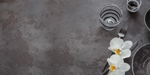 Réglage de la table d'élégance avec serviette grise tricotée, couverts, assiettes en céramique, verres et fleurs d'orchidées blanches sur table sombre. décoration de table moderne de vacances. dîner romantique.