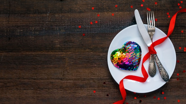 Réglage de la table de fête avec coeur arc-en-ciel sur une assiette blanche et des rubans rouges