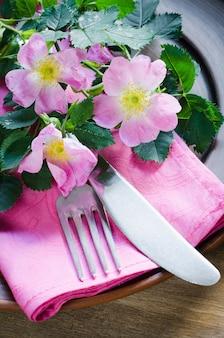 Réglage de la table de fête avec des fleurs roses.