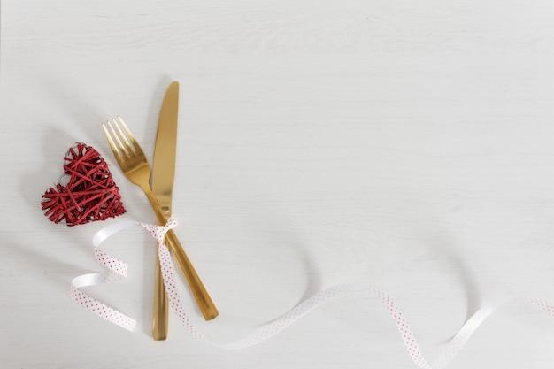 Réglage de la table de fête pour la saint-valentin avec une fourchette et un couteau et des décorations dorés.