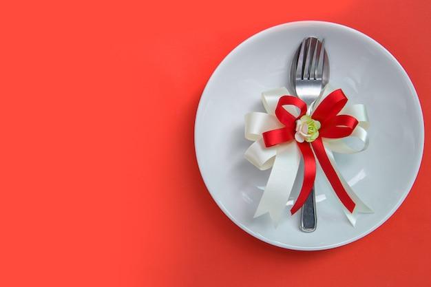 Réglage de la table de fête pour la saint-valentin avec fourchette et cuillère avec ruban sur un plat blanc sur fond rouge. copiez l'espace pour le texte. vue de dessus.