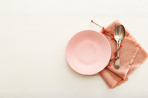 Réglage de la table de fête de la saint-valentin sur une table en bois blanche. dîner au restaurant à la saint-valentin. deux coeurs rouges sur plaque rose. saint valentin, amour, romance, concept de rencontres, espace de copie, mise à plat