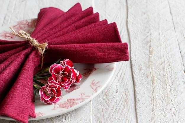 Réglage de la table avec des fleurs d'oeillets et une serviette rouge foncé