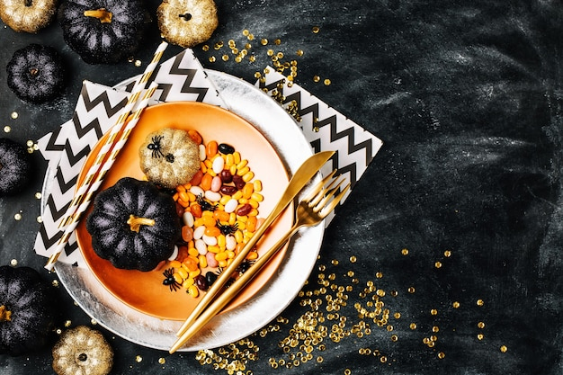 Réglage de la table d'halloween sur fond sombre. plat avec des bonbons s sur une table sombre avec citrouille noir et or. mise à plat, concept de vacances à la mode vue de dessus.