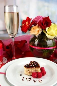 Réglage de la table en l'honneur de la saint-valentin sur la surface de la pièce