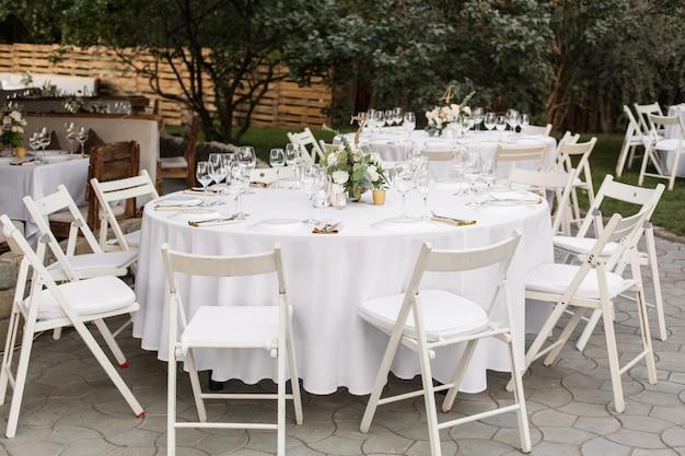Réglage de la table de mariage décoré de fleurs fraîches dans un vase en laiton