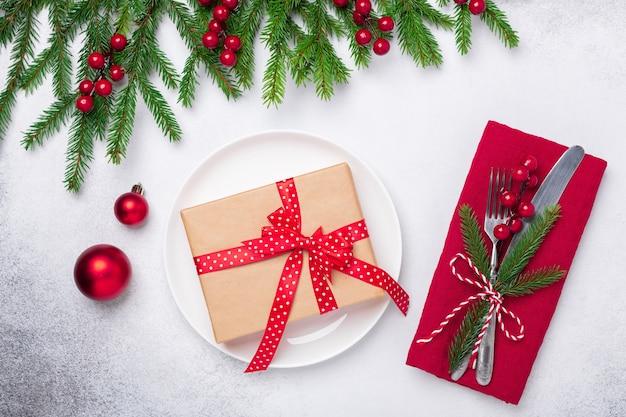 Réglage de la table de noël avec boîte cadeau et branche de sapin