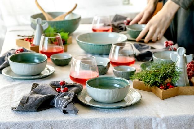 Réglage de la table de noël rustique avec vaisselle en céramique artisanale vide, assiettes et bols, décorations d'ange de noël, verres de jus rouge, branches vertes et baies sur nappe blanche devant la fenêtre