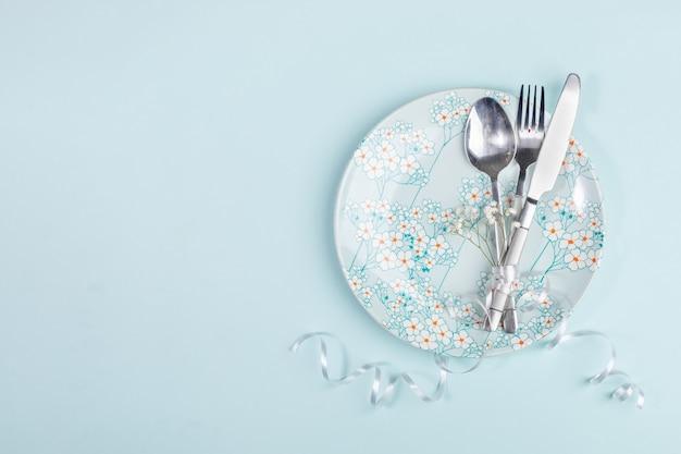 Réglage de la table de pâques avec couverts sur plaque bleu clair avec décor de fleurs de printemps sur bleu pastel.