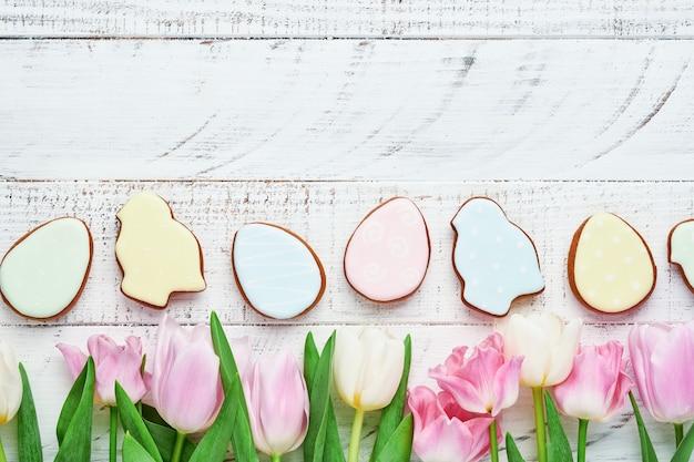 Réglage de la table de pâques avec décor floral et plaque avec pain d'épice de pâques sur table blanche. vue de dessus.