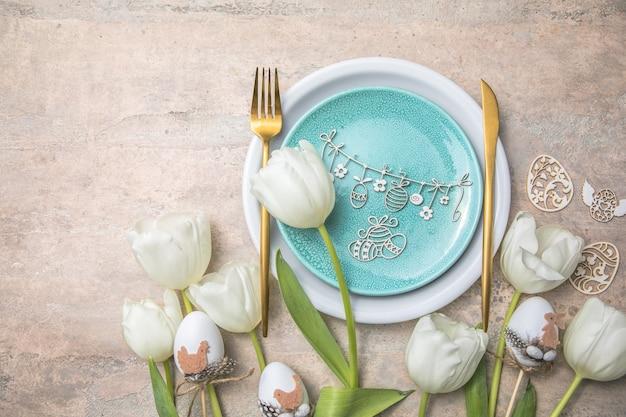 Réglage de la table de pâques avec décor floral sur table grise. dîner d'élégance