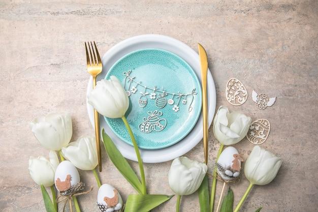Réglage de la table de pâques avec décor floral sur table grise.