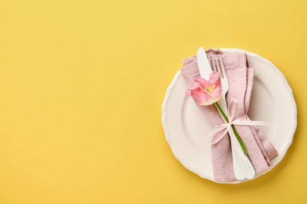 Réglage de la table de pâques avec décor floral sur table jaune. dîner d'élégance.