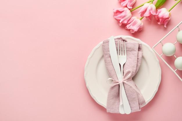 Réglage de la table de pâques avec décor floral sur table rose