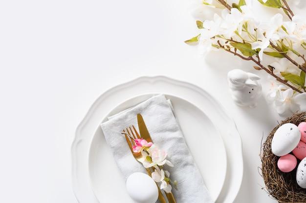Réglage de la table de pâques avec des fleurs épanouies sur un tableau blanc.