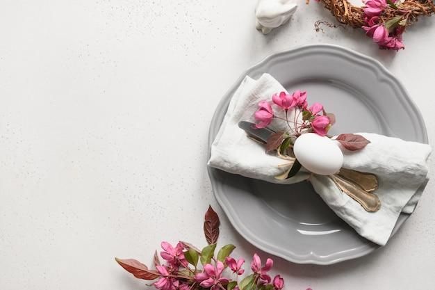 Réglage de la table de pâques avec des fleurs de pomme en fleurs sur un tableau blanc.