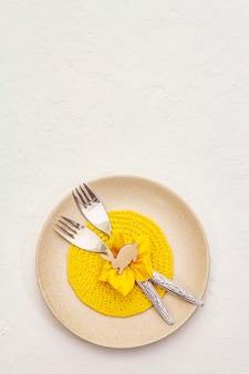 Réglage de la table de pâques sur fond de mastic blanc texturé. modèle de carte de vacances de printemps. couverts, serviette en tricot, fleur