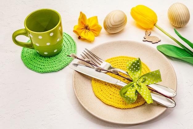 Réglage de la table de pâques sur fond de mastic blanc texturé. modèle de carte de vacances de printemps. couverts, serviette en tricot, œuf, lapin, tulipe, tasse à pois