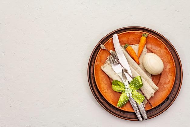 Réglage de la table de pâques sur fond de mastic blanc texturé. modèle de carte de vacances de printemps. couverts, serviette vintage, oeuf, carotte, lapin