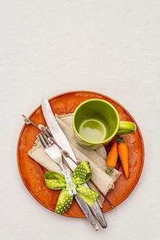 Réglage de la table de pâques sur fond de mastic blanc texturé. modèle de carte de vacances de printemps. couverts, tasse, serviette vintage, oeuf, carotte, lapin