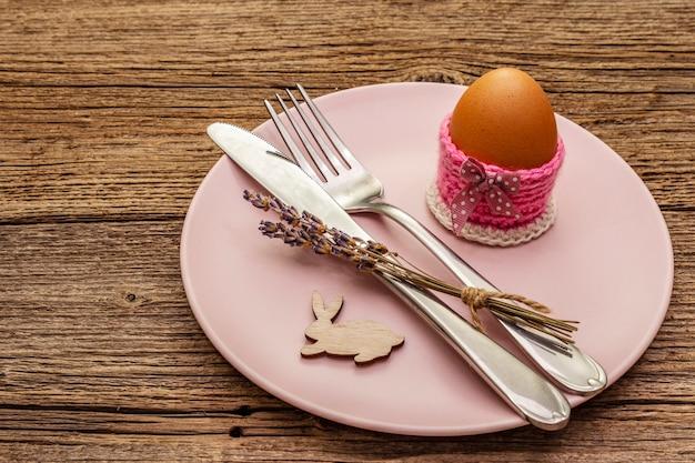 Réglage de la table de pâques sur fond de planches en bois vintage. modèle de carte de vacances de printemps. couverts, oeuf, lavande, lapin, support tricoté