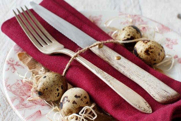 Réglage de la table de pâques avec des œufs de caille et des plumes