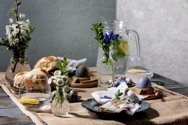Réglage de la table de pâques avec des œufs colorés et en chocolat, petits pains chauds, bouquet de fleurs, assiette en céramique vide avec serviette, verre de limonade sur table en bois avec nappe textile.