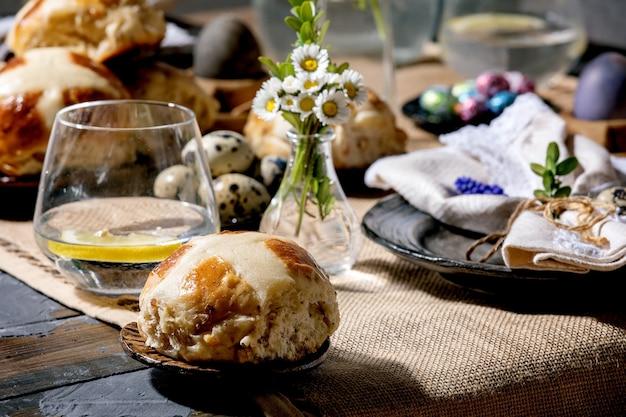 Réglage de la table de pâques avec des oeufs colorés et en chocolat, petits pains chauds, bouquet de fleurs, assiette en céramique vide avec serviette, verre de limonade sur table en bois avec nappe textile