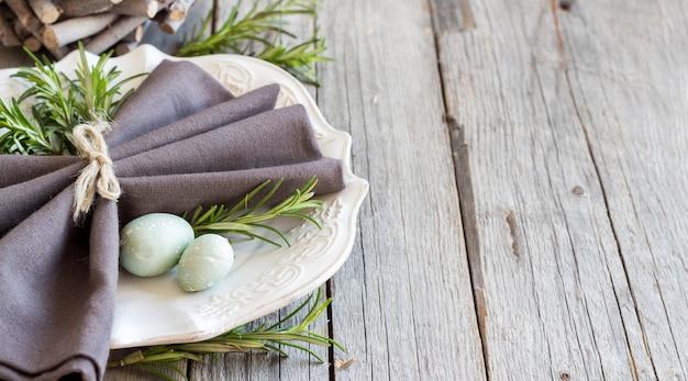 Réglage de la table de pâques avec des œufs et du romarin sur une table en bois gris bouchent avec copie espace
