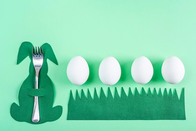 Réglage de la table de pâques. porte-couverts créatif drôle mignon en forme de lapin vert et oeufs blancs sur fond vert. bricolage et créativité des enfants. fond de pâques avec espace de copie pour le texte.