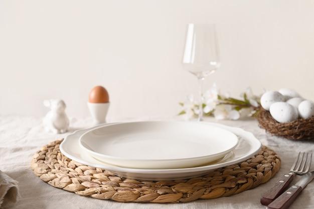 Réglage de la table de pâques de printemps avec des œufs biologiques, des lapins et des fleurs épanouies.