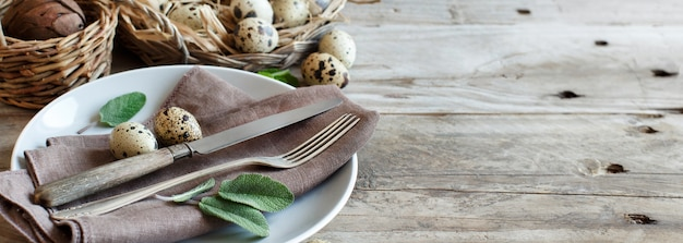 Réglage de la table de pâques rustique avec des œufs et des herbes sur une table en bois