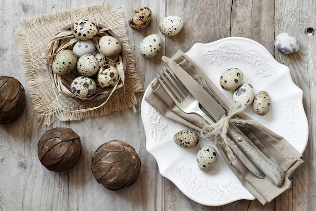 Réglage de la table de pâques rustique avec des œufs sur une table en bois