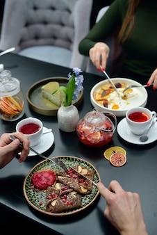 Réglage de la table de petit déjeuner avec des crêpes, du thé. couple mange