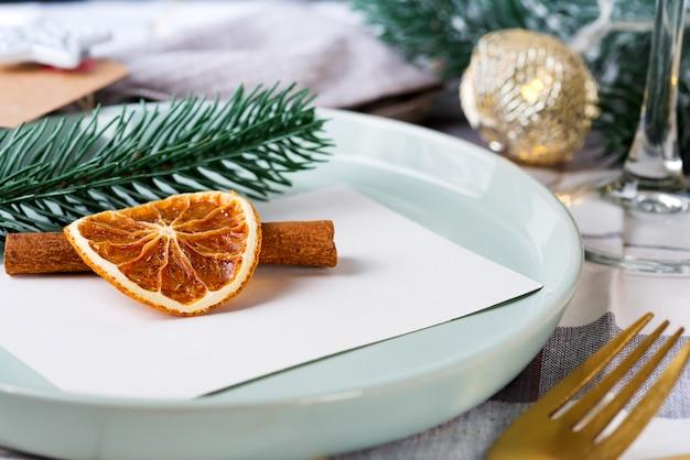 Réglage de la table pour les détails de noël et du nouvel an avec orange séchée et cannelle sur un tissu gris. salle à manger décorée