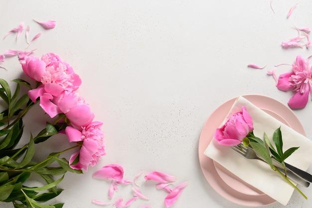 Réglage de la table de printemps avec des fleurs de pivoine rose sur un tableau blanc. vue d'en-haut.
