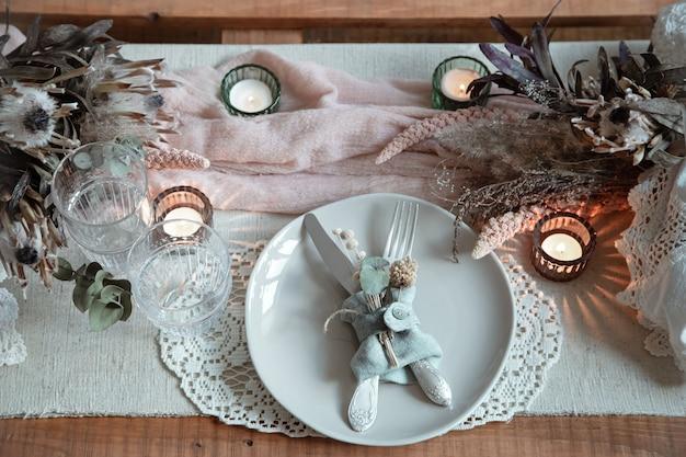 Réglage de la table romantique avec des bougies allumées et des fleurs séchées