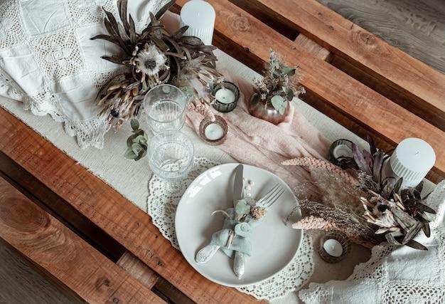Réglage de la table romantique avec des bougies et des fleurs séchées