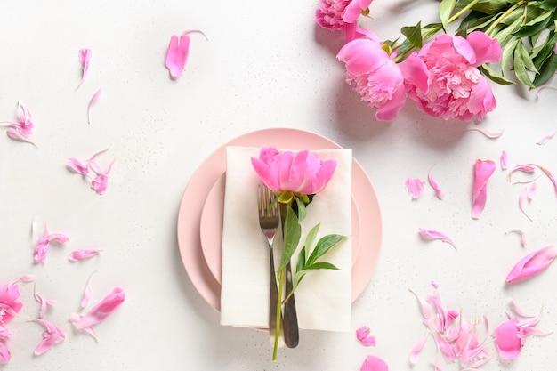 Réglage de la table romantique avec des fleurs de pivoine rose sur une table blanche vue d'en haut