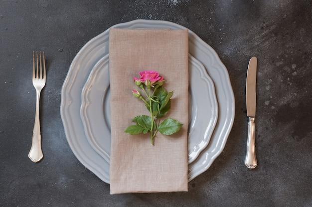 Réglage de la table romantique avec des roses roses comme décor, vaisselle vintage, argenterie.