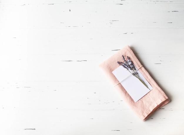 Réglage de la table romantique rustique avec carte en papier, serviette rose, lavande sur table en bois blanc. vue de dessus.