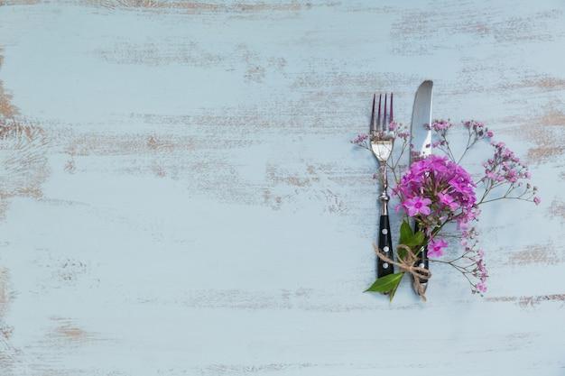 Réglage de la table rustique avec des fleurs roses sur une table en bois clair. décoration de vacances sur le style provençal. dîner romantique. vue de dessus avec espace de copie pour le texte