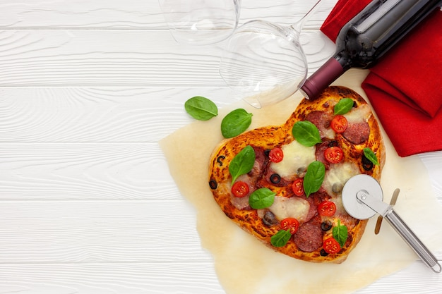 Réglage de la table de la saint-valentin. pizza au coeur avec du vin et des verres