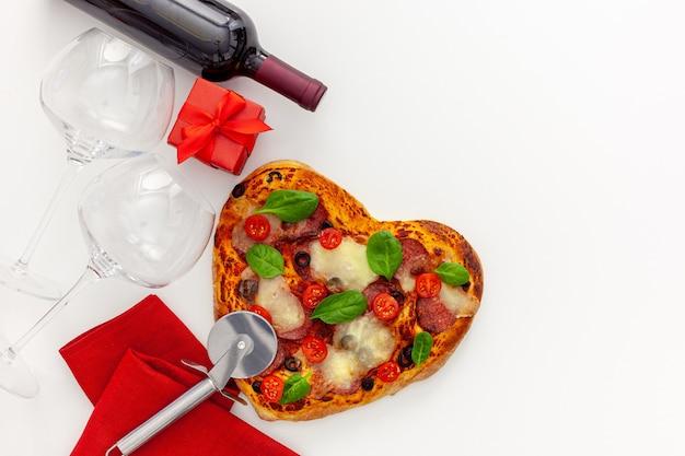Réglage de la table de la saint-valentin. pizza coeur avec vin, verres et coffret cadeau
