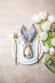 Réglage de la table de vacances de pâques avec lapin d'oeuf sur plaque blanche et fleurs de tulipes.
