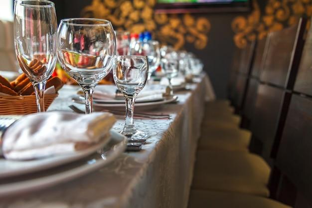 Réglage de la table avec des verres, des assiettes, des serviettes et de la nourriture