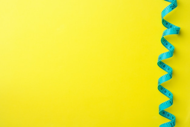 Règle centimétrique pliée avec compartiments de mesure sur fond jaune.