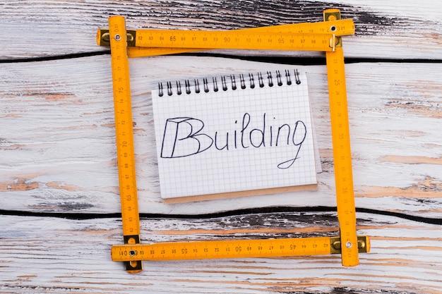 Règle de charpentier en plastique jaune carré sur fond de bois blanc. vue de dessus à plat.